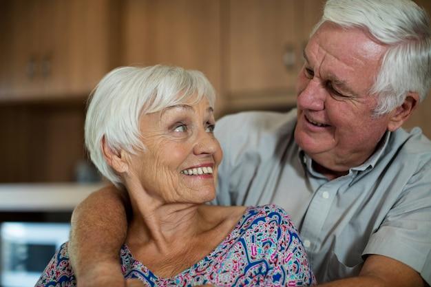 Casal feliz de idosos se abraçando na cozinha de casa
