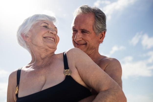 Casal feliz de idosos se abraçando na praia