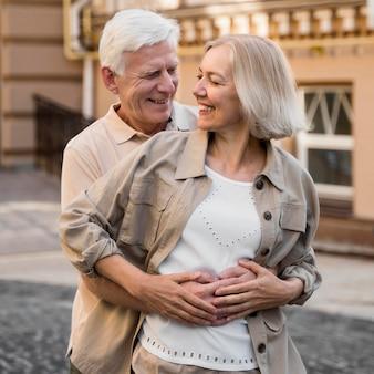 Casal feliz de idosos se abraçando romanticamente na cidade