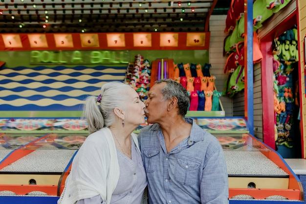 Casal feliz de idosos se beijando perto de uma barraca de jogo