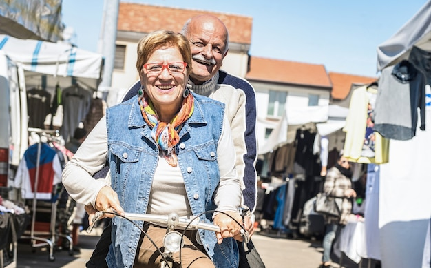 Casal feliz de idosos se divertindo de bicicleta no mercado da cidade