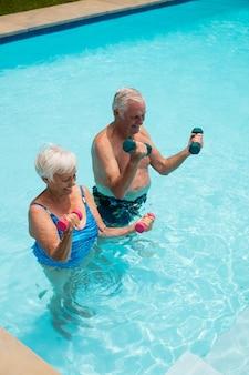 Casal feliz de idosos se exercitando com halteres na piscina
