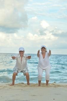 Casal feliz de idosos se exercitando no verão na praia