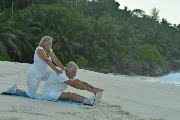 Casal feliz de idosos se exercitando no verão na praia Foto Premium
