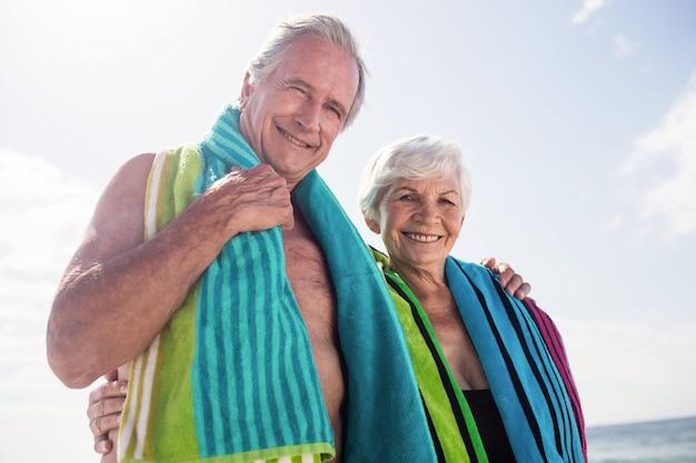 Casal feliz de idosos segurando uma toalha no pescoço