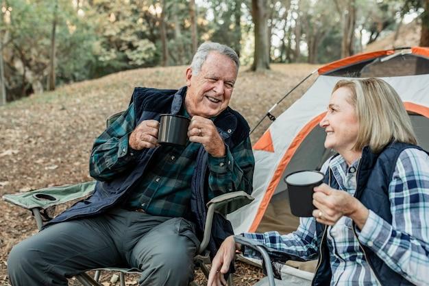 Casal feliz de idosos tomando café perto da barraca na floresta