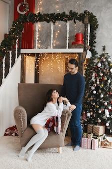 Casal feliz de jovens amantes posando perto de árvore de natal na sala decorada para o ano novo ho ...