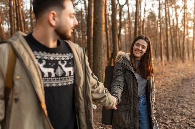 Casal feliz de mãos dadas na floresta