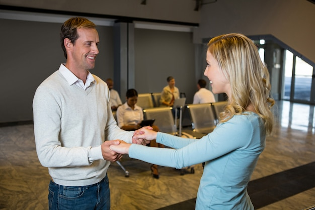 Casal feliz de mãos dadas na sala de espera