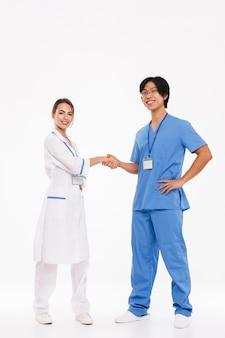 Casal feliz de médicos vestindo uniforme em pé, isolado na parede branca, apertando as mãos