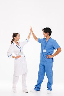 Casal feliz de médicos vestindo uniforme em pé, isolado na parede branca, dando mais cinco