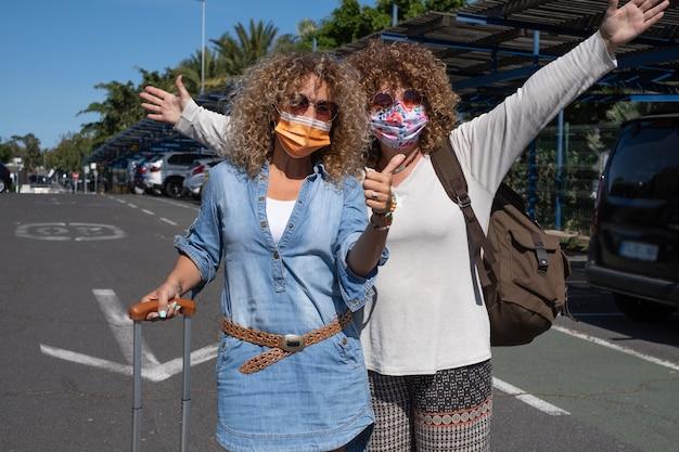 Casal feliz de mulheres encaracoladas no estacionamento do aeroporto com malas e mochilas prontas para viajar