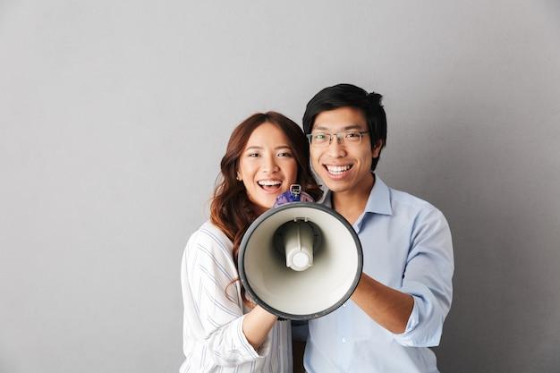 Casal feliz de negócios asiáticos isolado, segurando um alto-falante