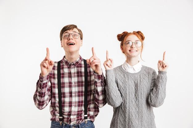 Casal feliz de nerds da escola apontando o dedo
