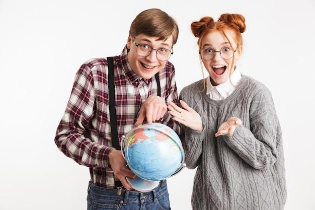 Casal feliz de nerds escolares segurando um globo terrestre