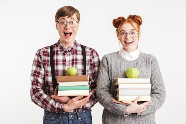 Casal feliz de nerds escolares segurando uma pilha de livros