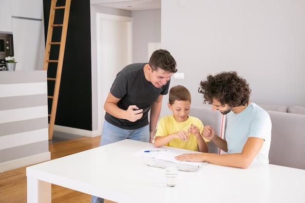 Casal feliz de pais ajudando o menino focado com as tarefas escolares em casa, sentados à mesa juntos, escrevendo no papel. conceito de família e pais gays