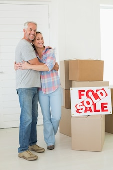 Casal feliz de pé e abraçando ao lado do sinal vendido