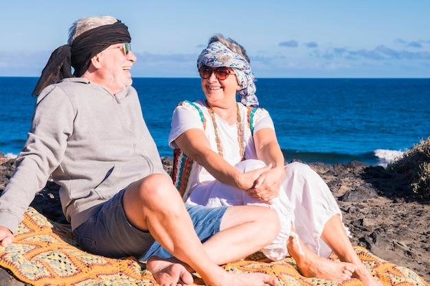 Casal feliz de pessoas sênior, cavalheiro e senhora, senta-se perto do oceano com estilo hippie de roupas coloridas. aproveite e divirta-se com um estilo de vida alternativo. pessoas brancas alegres curtindo o vacatio