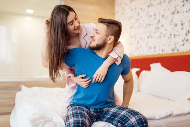 Casal feliz de pijama relaxando na cama em casa, bom dia. relacionamento harmonioso em uma jovem família