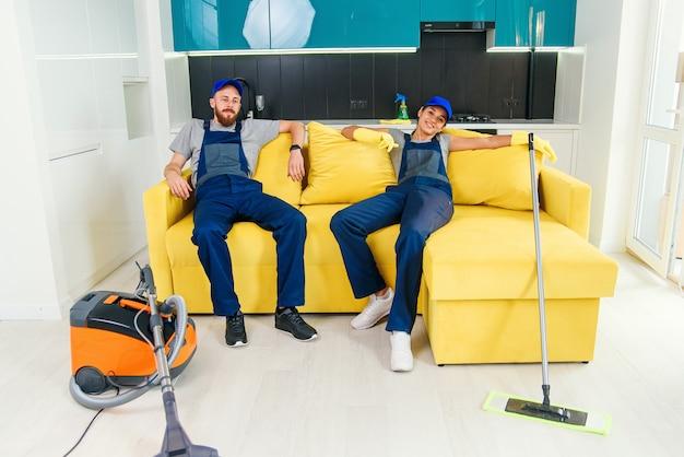Casal feliz de produtos de limpeza profissionais, descansando no sofá depois de limpar a cozinha.