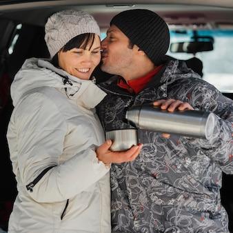 Casal feliz de tiro médio com garrafa térmica