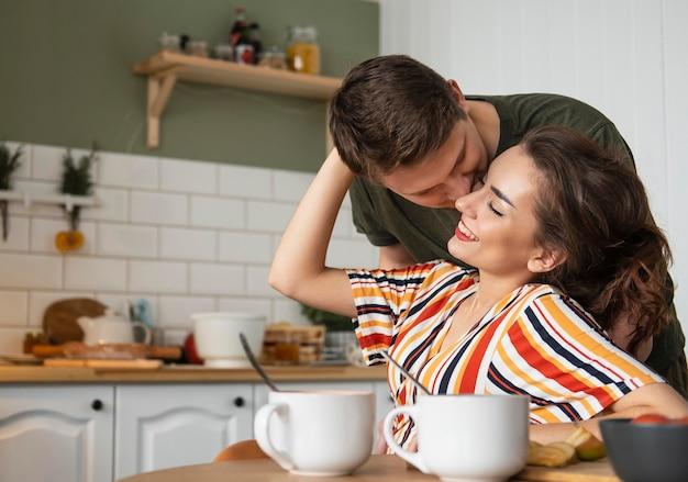 Casal feliz de tiro médio com xícara de café