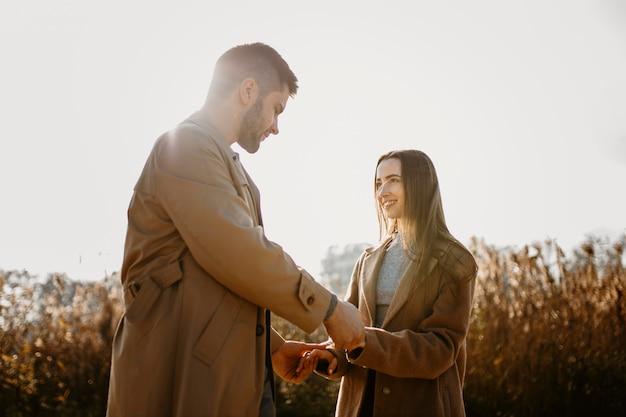 Casal feliz de tiro médio de mãos dadas