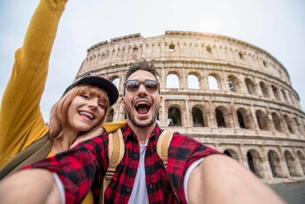 Casal feliz de turista se divertindo tomando uma selfie na frente do coliseu, em roma.
