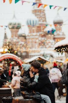 Casal feliz de turistas se beijando ao lado da catedral de são basílio