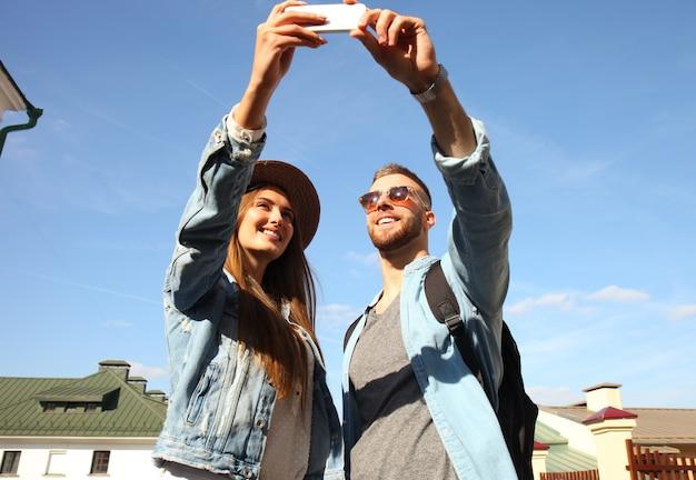 Casal feliz de turistas tomando selfie na cidade velha.