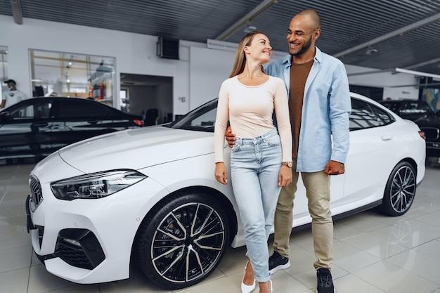 Casal feliz de uma mulher caucasiana e um homem afro-americano em pé perto de seu novo carro de luxo dentro do salão do carro.