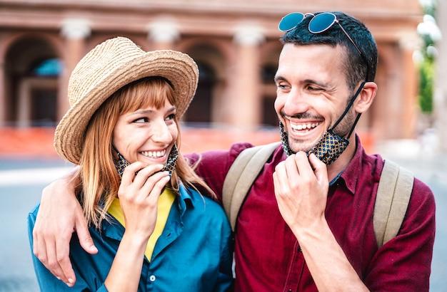 Casal feliz de viagens sorrindo com máscara aberta