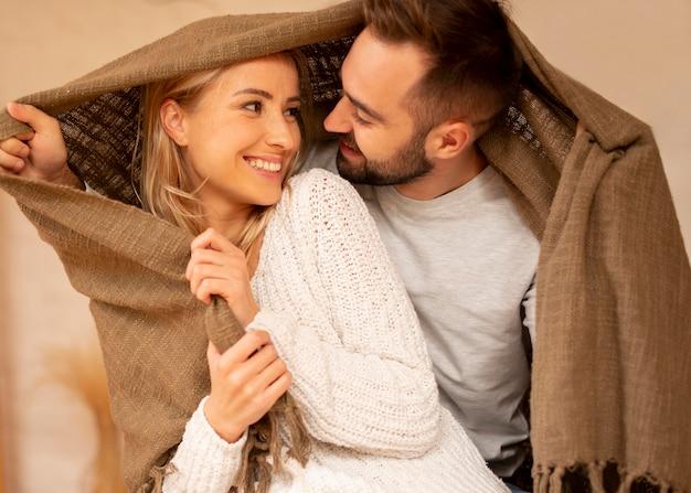 Casal feliz debaixo do cobertor
