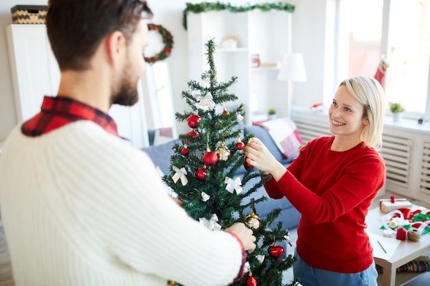 Casal feliz decorando a árvore de natal