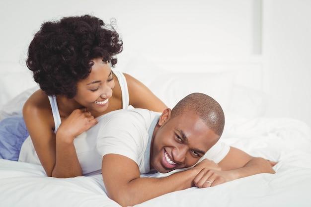 Casal feliz deitada na cama em casa