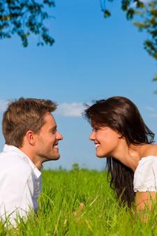Casal feliz, deitado em um campo ensolarado, olhando um ao outro