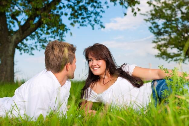 Casal feliz, deitado em um pasto, olhando um ao outro