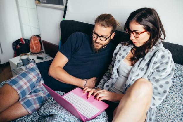 Casal feliz, deitado na cama interior olhando para o computador
