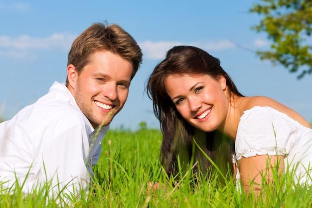 Casal feliz, deitado na grama em um campo ensolarado