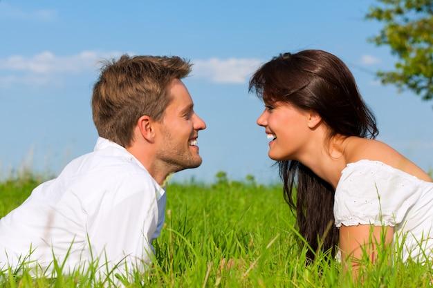 Casal feliz, deitado na grama, olhando um ao outro