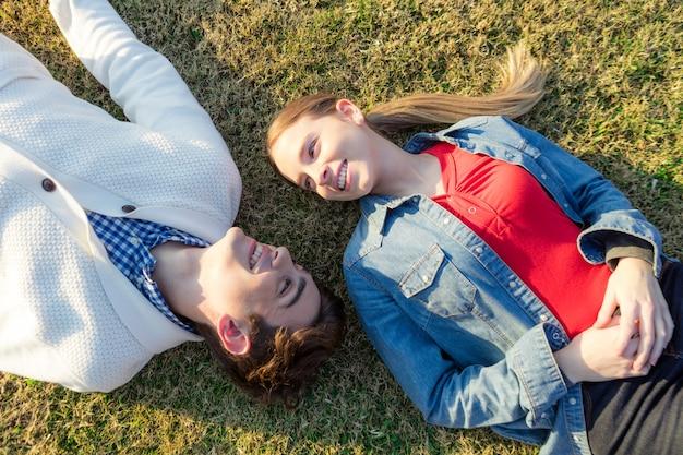 Casal feliz deitado na grama