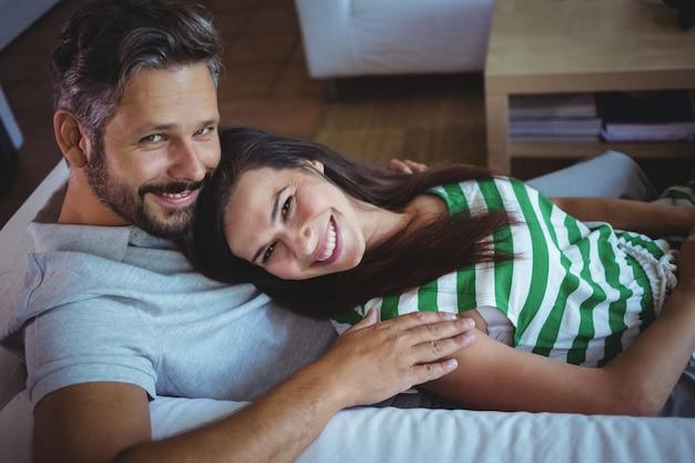 Casal feliz, deitado no sofá na sala de estar