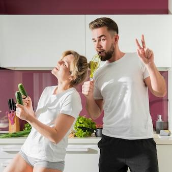 Casal feliz dentro de casa, cantando e dançando