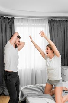 Casal feliz dentro de casa jogando juntos