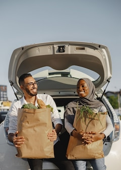 Casal feliz diversificado se divertindo depois de fazer compras. sentado no porta-malas do carro cheio de alimentos frescos e saudáveis.