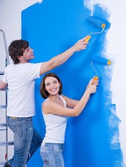 Casal feliz e alegre com rolos pintando a parede - dentro de casa