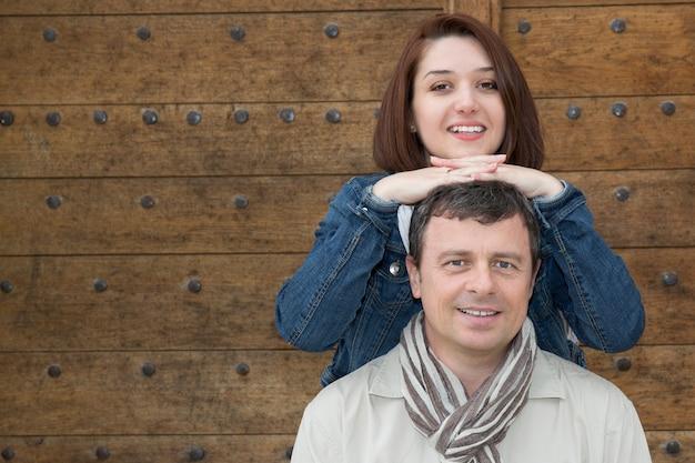 Casal feliz e amoroso, abraçando na frente do portão de madeira