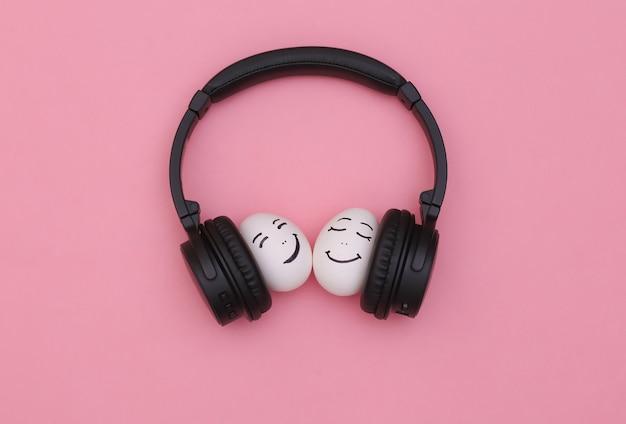 Casal feliz e amoroso com duas caras de ovo ouvindo música em fones de ouvido no fundo rosa