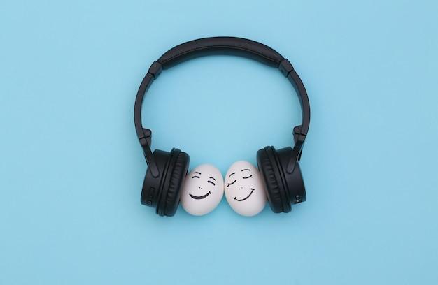 Casal feliz e amoroso de rostos de ovos ouve música em fones de ouvido sobre fundo azul